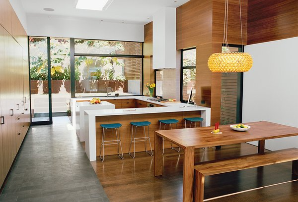 Bernstein specified sequenced walnut veneers in the kitchen and dining area and counters from Caesarstone. The Chrysalis bar stool is by One & Co for Council. A Foscarini pendant hangs above Ligne Roset's Eaton table and bench.