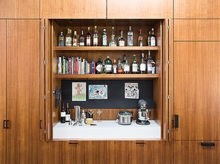 At a home in San Francisco, the non-visible modern cabinet door hinges of this bar and surrounding cabinetry are due to the frameless cabinets and hinges that mount directly to the interior of the cabinet.