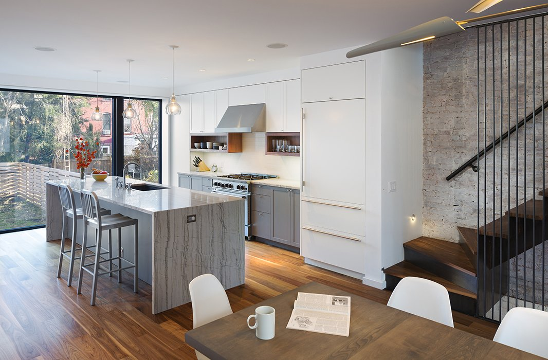 Large, rear-facing windows connect Darrow and Folch's kitchen to the backyard.  Photo 6 of 10 in Get an Advance Look at the Amazing Residences on Dwell's Brooklyn Home Tour