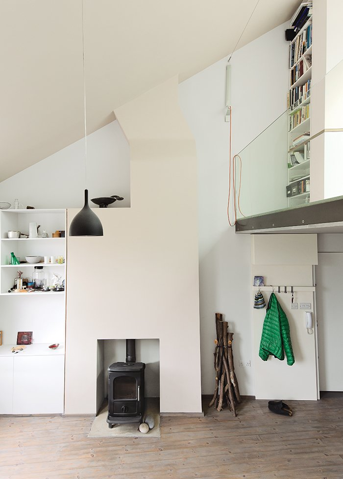 Living Room, Wood Burning Fireplace, Light Hardwood Floor, Pendant Lighting, Storage, and Shelves Architects Silvia Ullmayer and Allan Sylvester worked with joiner Roger Hynam to reinvent an apartment for metalworker Simone ten Hompel.  Modern Wood-Burning Stoves by Megan Hamaker from This Is How You Can Live Large in a Small Space