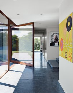 A custom pivot door by Archispec opens onto a foyer with a poured-concrete floor. The oil painting at right is by Derrick Buisch.