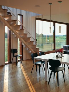 Stainless-steel cables along the stairs function as a second railing without blocking views through the adjacent windows.