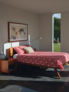 In the bedroom, Tolomeo wall lamps from Artemide are mounted on both sides of the Astrid bed by Copeland. The coral Trellis duvet cover and pillow cases are by Trina Turk Residential.