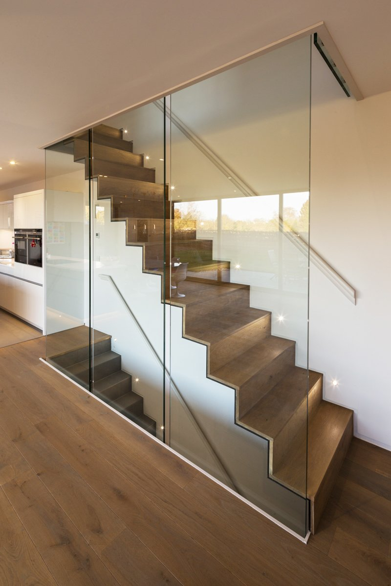 The home's ground level features engineered oak flooring. The staircase, which leads to the house's upper and lower levels, was constructed out of steel folded plate and subsequently clad in timber.  Modern Glass-Encased Staircases by Brandi Andres from Sandpath