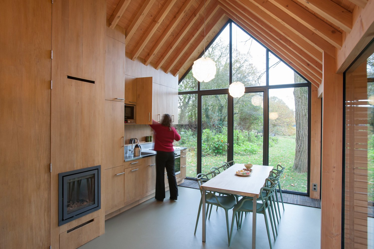 Kitchen and Wood Cabinet Fine wood craftsmanship defines the dwelling's interior, where all the facilities—from the kitchen cabinets to the fireplace to the bathroom—are integrated into a single oak wall, handmade by van Norel. He also made the dining table, which is paired with Philippe Starck master chairs—the only ready-made items in the space other than fixtures and appliances.  Utrecht Cabin by Laura C. Mallonee from Light-Filled Dining Rooms