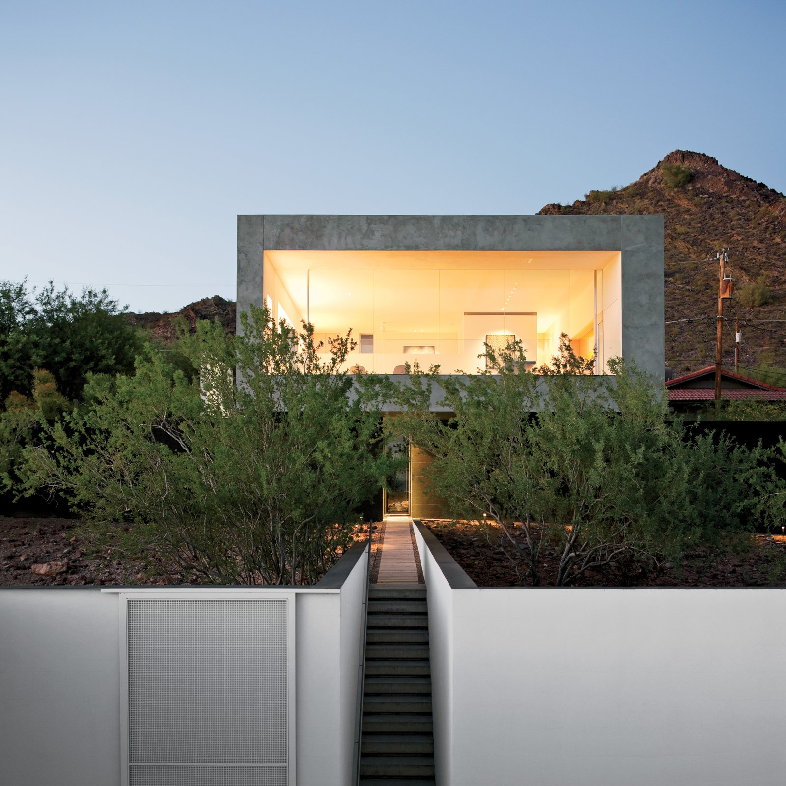 """Exterior, Concrete Siding Material, and Flat RoofLine """"The challenge was to render the site whole again after the original owner 'bladed' most of the creosote bush,"""" explains Debra Burnette, who concieved the landscape design.  Photo 3 of 8 in This House Doesn't Hold Back and Embraces the Desert"""
