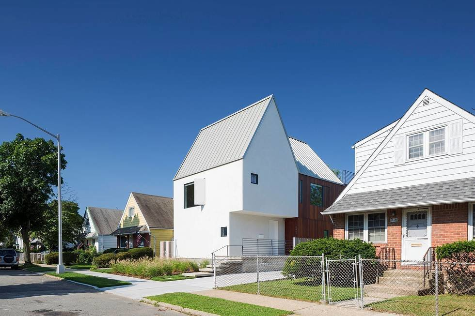 """With clean white stucco cladding and unusual angles, the three-module house stands out from the surrounding neighborhood, which features mostly post-war, one-and-a-half story homes.  All the """"Right"""" Angles from Three Unique Homes Fit Under One Roof for an Extended Family in Queens"""