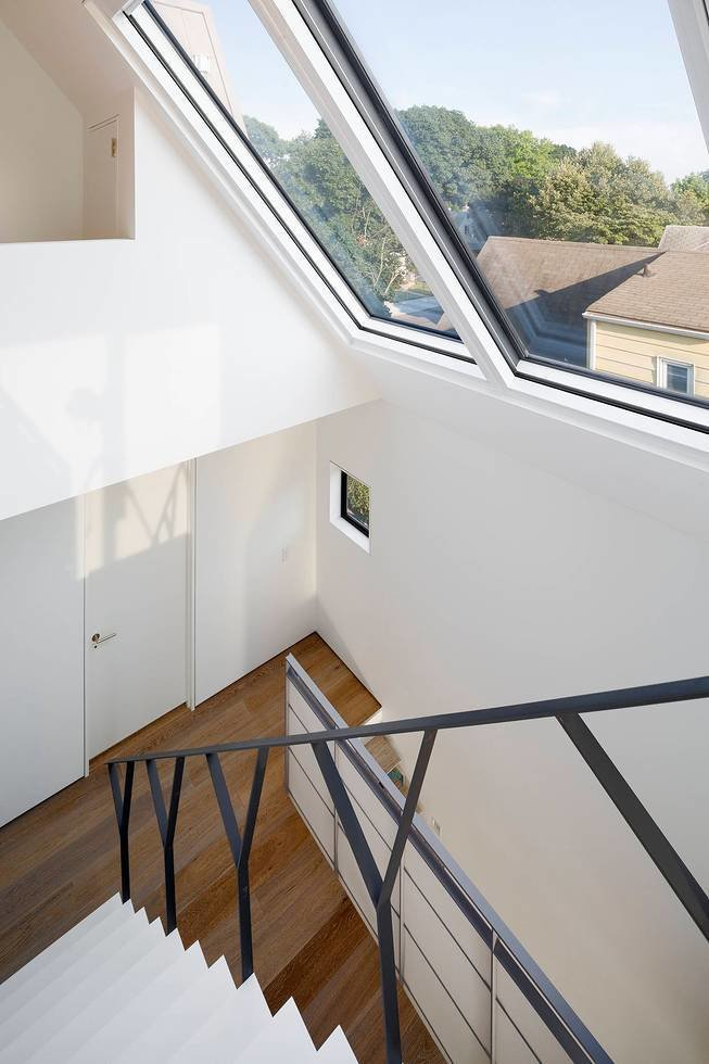 A thin Y-shaped metal banister guides movement up the stairs to the client's son's room. Below the Corian stairs, an office nook was carved out of the wall in the daughter's room.  190+ Best Modern Staircase Ideas from Three Unique Homes Fit Under One Roof for an Extended Family in Queens
