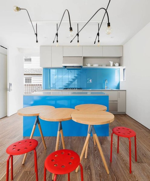 O'Neill Rose Architects designed each unit of this modern Queens compound based on the personality of the family member occupying it. The kitchen in the brother's unit is bright and fun with a backsplash made of painted glass. The light fixtures, like many other materials found in the project, were left over from the client's contracting work; O'Neill Rose bent the found pipes into an array of angles and attached light bulbs.