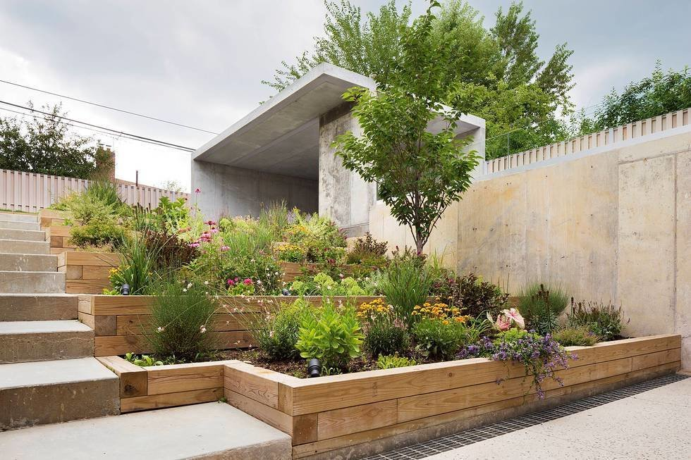 The backside of the lot was dug out to create a recessed garden for privacy. The mother is an active cook, so including planter boxes for herbs and hot peppers was a must.  Backyard Daydream from Three Unique Homes Fit Under One Roof for an Extended Family in Queens