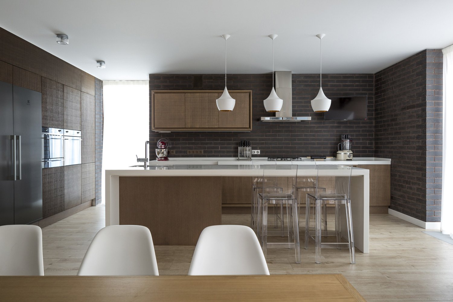 """""""The interior design is restrained, sometimes minimalist, but very expressive,"""" Zhidkov says. The space is outfitted with modern pieces like the Eames Eiffel chairs, lucite bar stools, and geometric pendant lights.  House in Moscow by Laura C. Mallonee"""