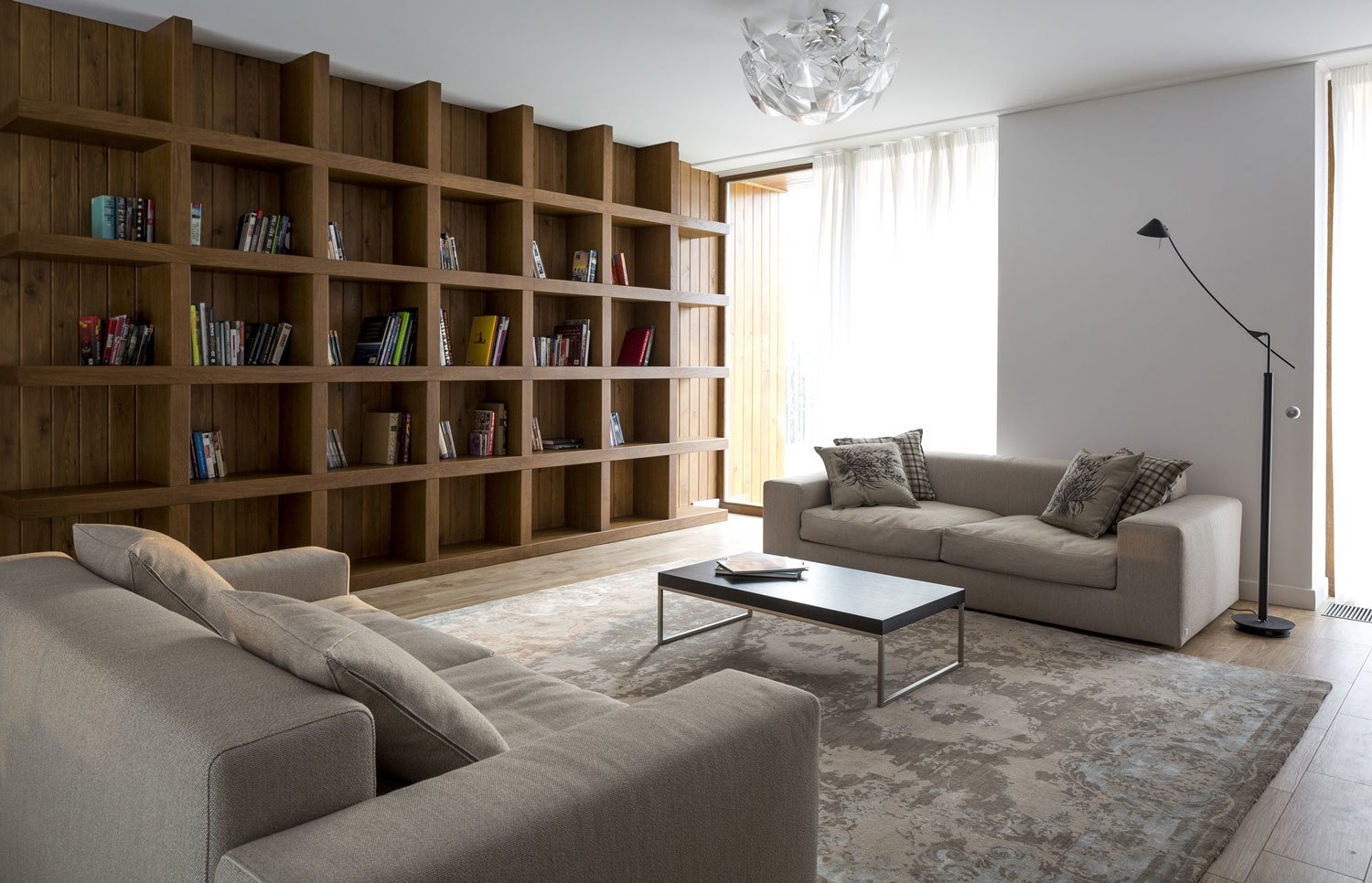 A built-in larch bookshelf occupies an entire wall on the second floor den.  House in Moscow by Laura C. Mallonee