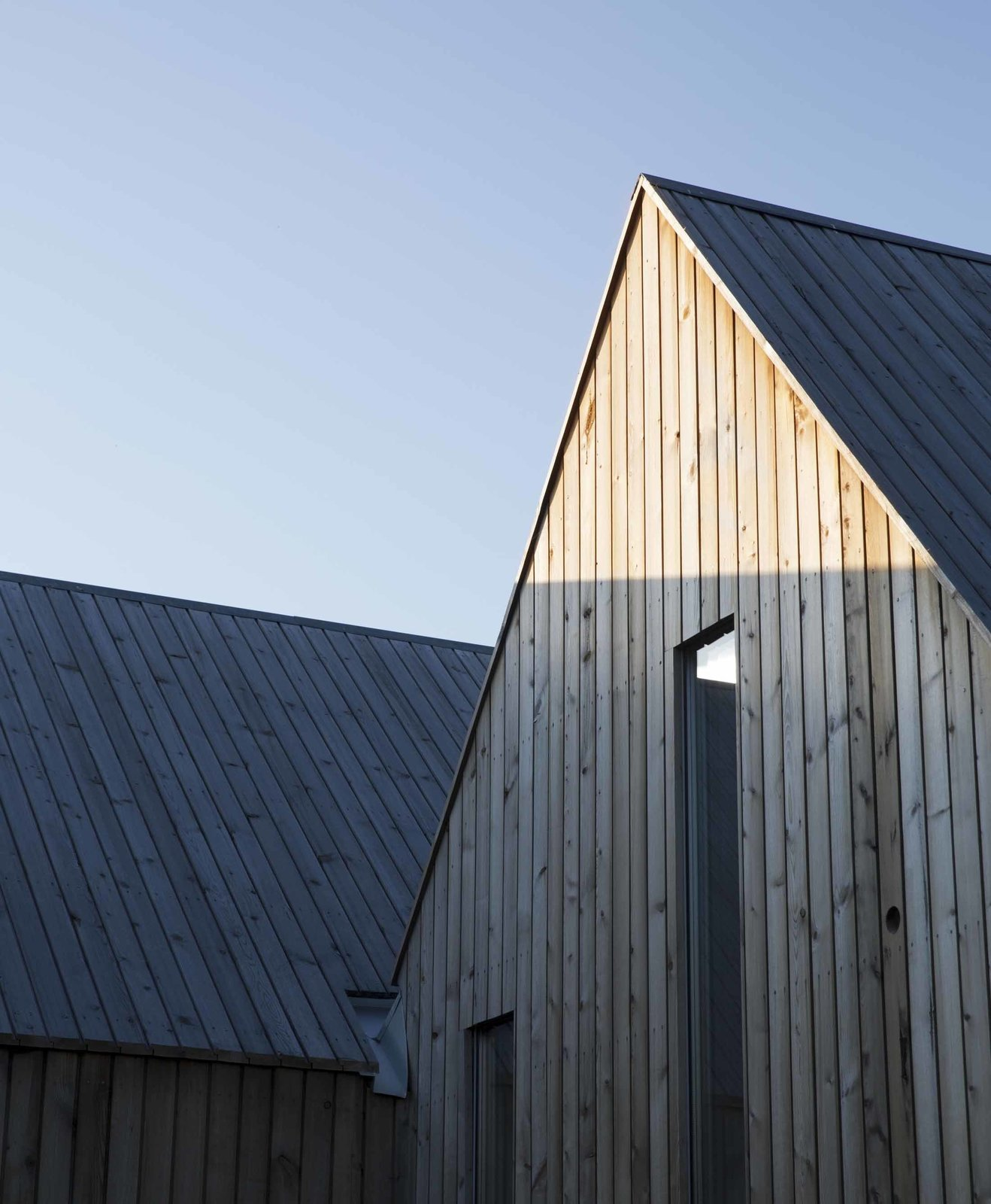 Exterior, House Building Type, and Gable RoofLine With their matching peaked roofs, every cabin nods to the traditional form of countryside retreats. The cluster's pine cladding has been treated to speed up the aging process, giving it a warm patina.  Photo 6 of 6 in This Cozy Retreat Holds the Cure for Cabin Fever