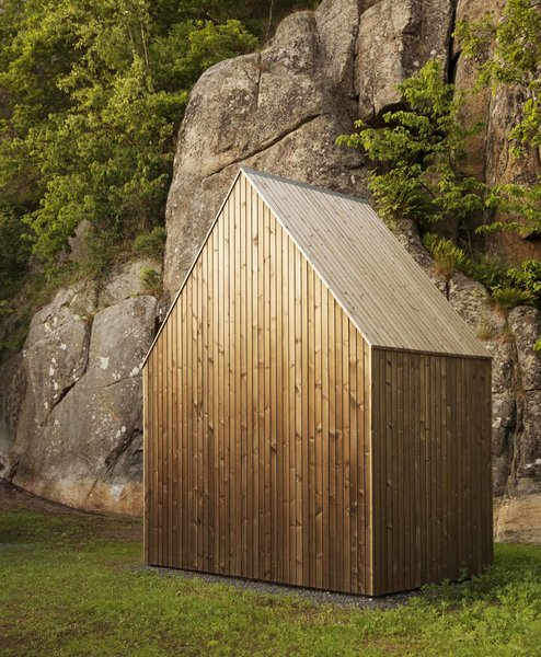 A shed provides storage for the owners' tools as well as wood for the fireplace. It features the same aged pine finish as the main home.
