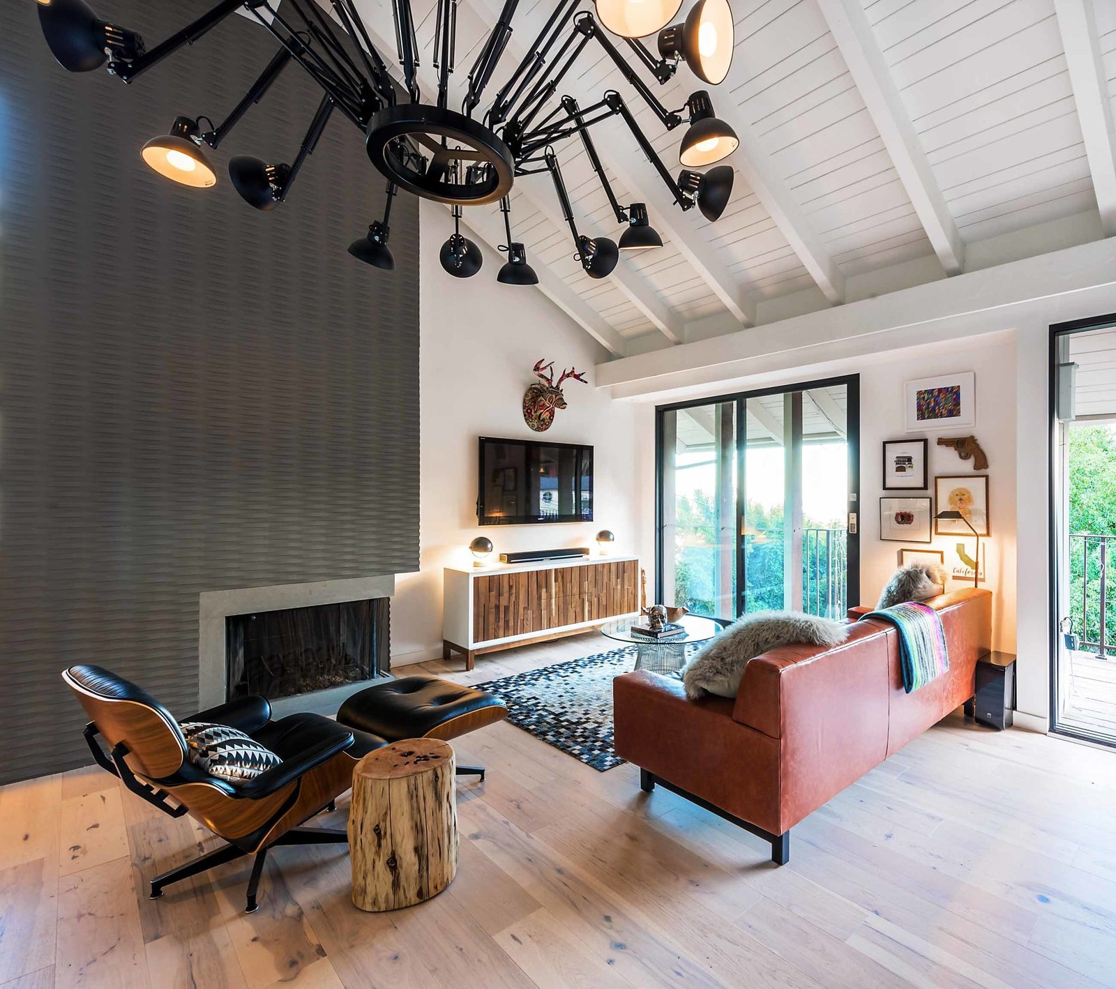 The main focal point of the living area is the oversized, spider-like chandelier—a bold statement that lights up the room. The furniture was sourced locally whenever possible, like the custom media cabinet from Weego Home, made with walnut.  Photo 2 of 6 in Playful Materials Refresh a Dated Hollywood Home