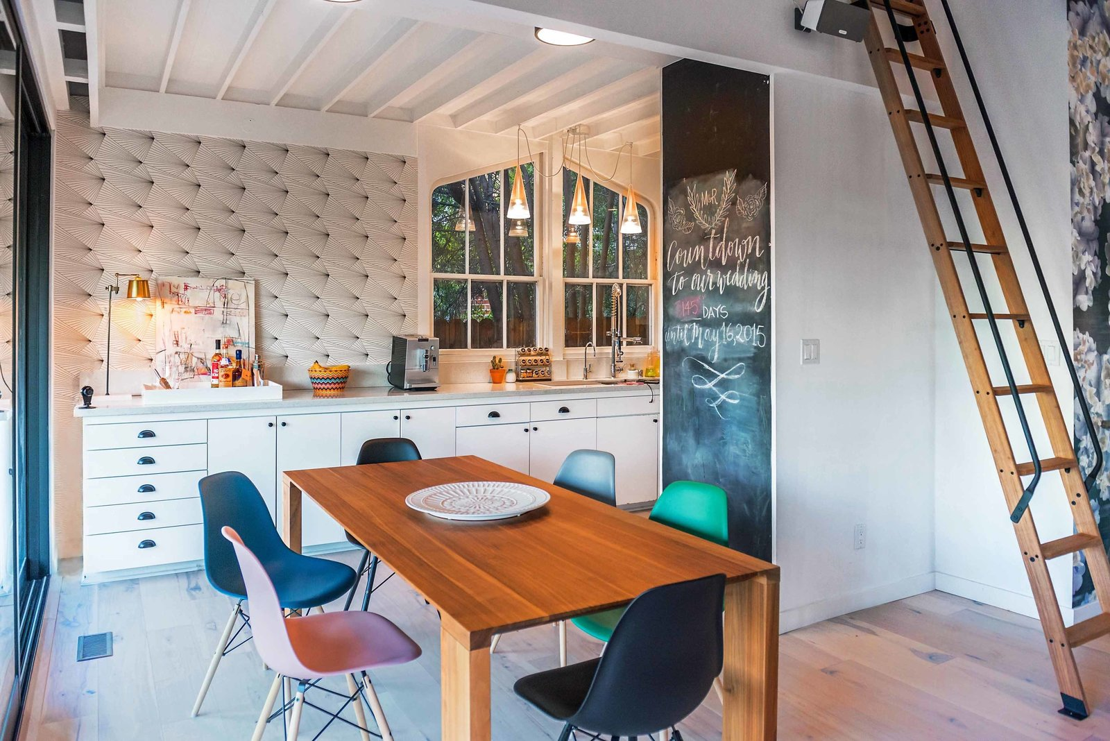 The kitchen is just as detailed and eclectic as the rest of the main floor, with a wall-sized chalkboard and retro wallpaper accenting the streamlined white cabinetry. Bright, colorful dining room chairs add whimsy.  Photo 10 of 42 in Wallpaper That Fixes Walls
