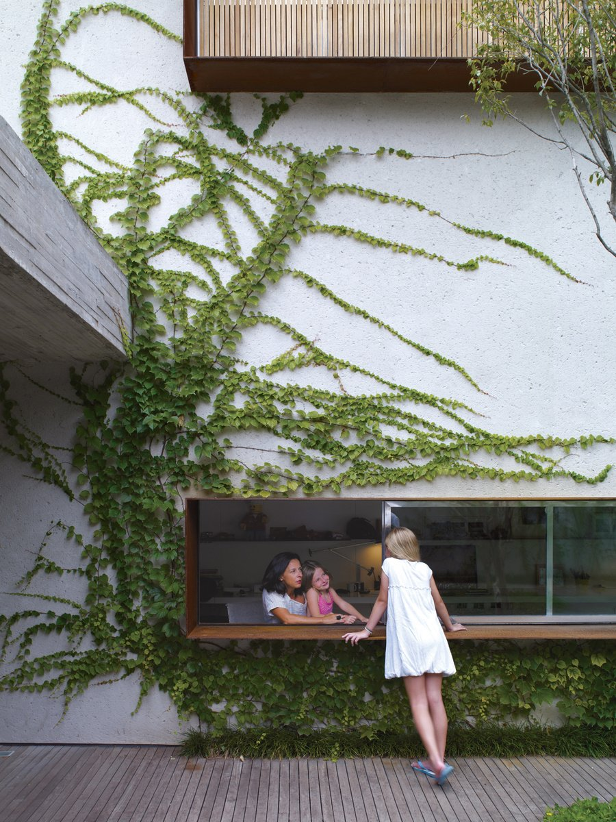 From the garden deck, Sophia Cóser talks to sister Helena and mother Piti through a wide, low-slung window typical of architect Marcio Kogan. Photo by Cristobal Palma.  Composition from Destination of the Week: São Paulo