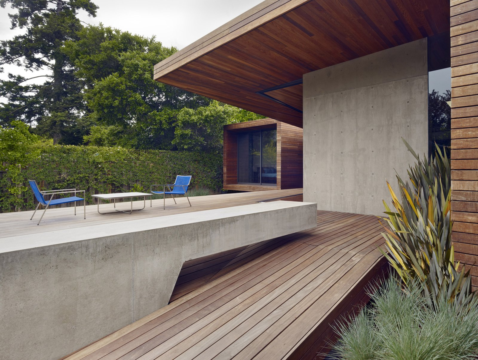 Outdoor, Large Patio, Porch, Deck, Wood Patio, Porch, Deck, Concrete Patio, Porch, Deck, and Shrubs A spacious deck was created as part of the addition. A cantilevered concrete bench stretches out to the rear garden and complements the adjacent concrete wall.  Concrete