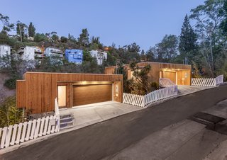 The two separate structures were given a visual unity by cladding them with a specially fire-treated cedar siding on the exterior. The white picket fence is another visual tie between the properties.