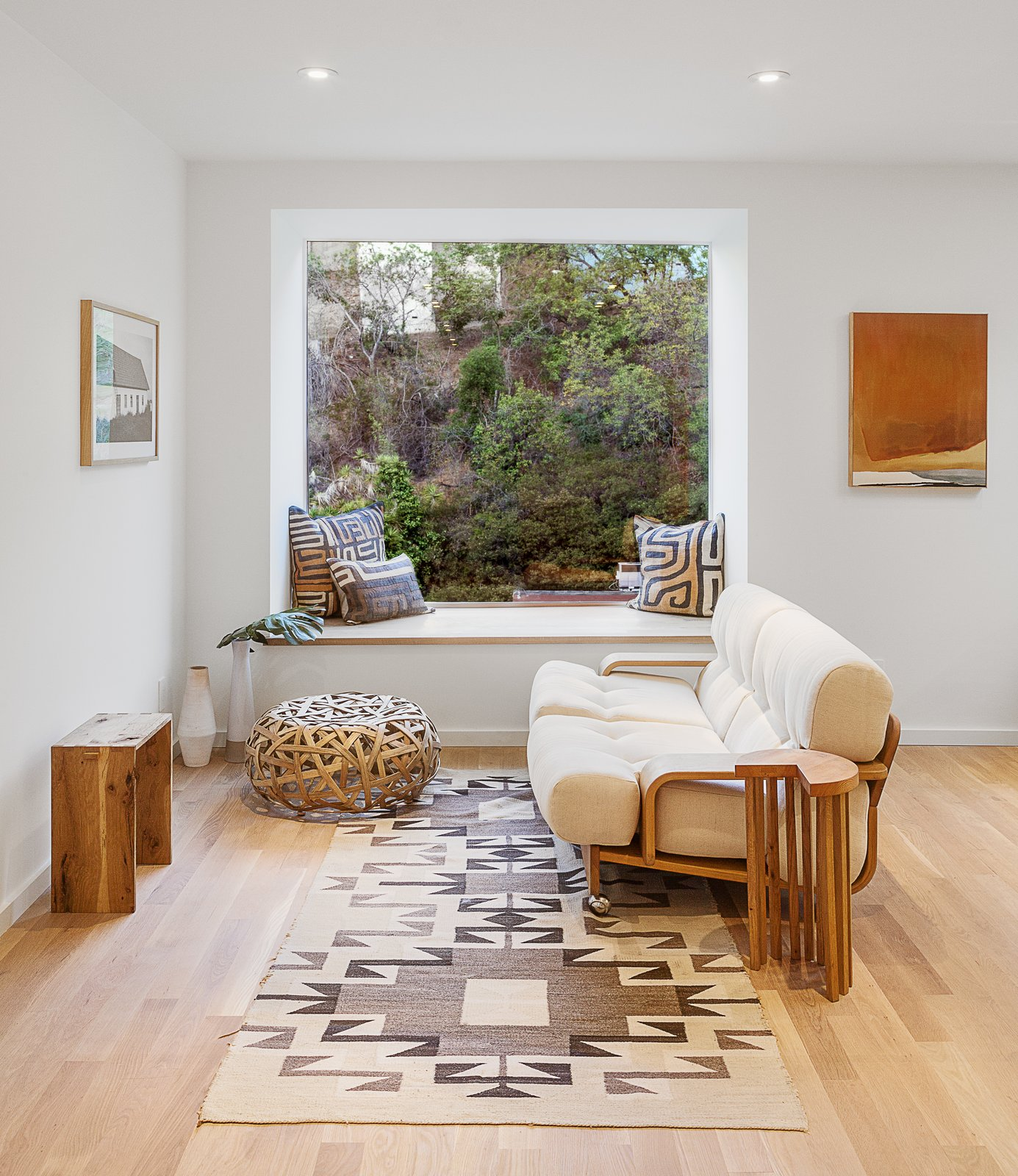 """The lounge setup shows one of five """"bump-outs"""" — in this case, it is used to provide additional seating without taking up floor space. In other parts of the house, the built-in seats also provide extra sleeping areas.  Photo 6 of 9 in Twin Houses on Tiny Lots Stretch Outward for Space"""