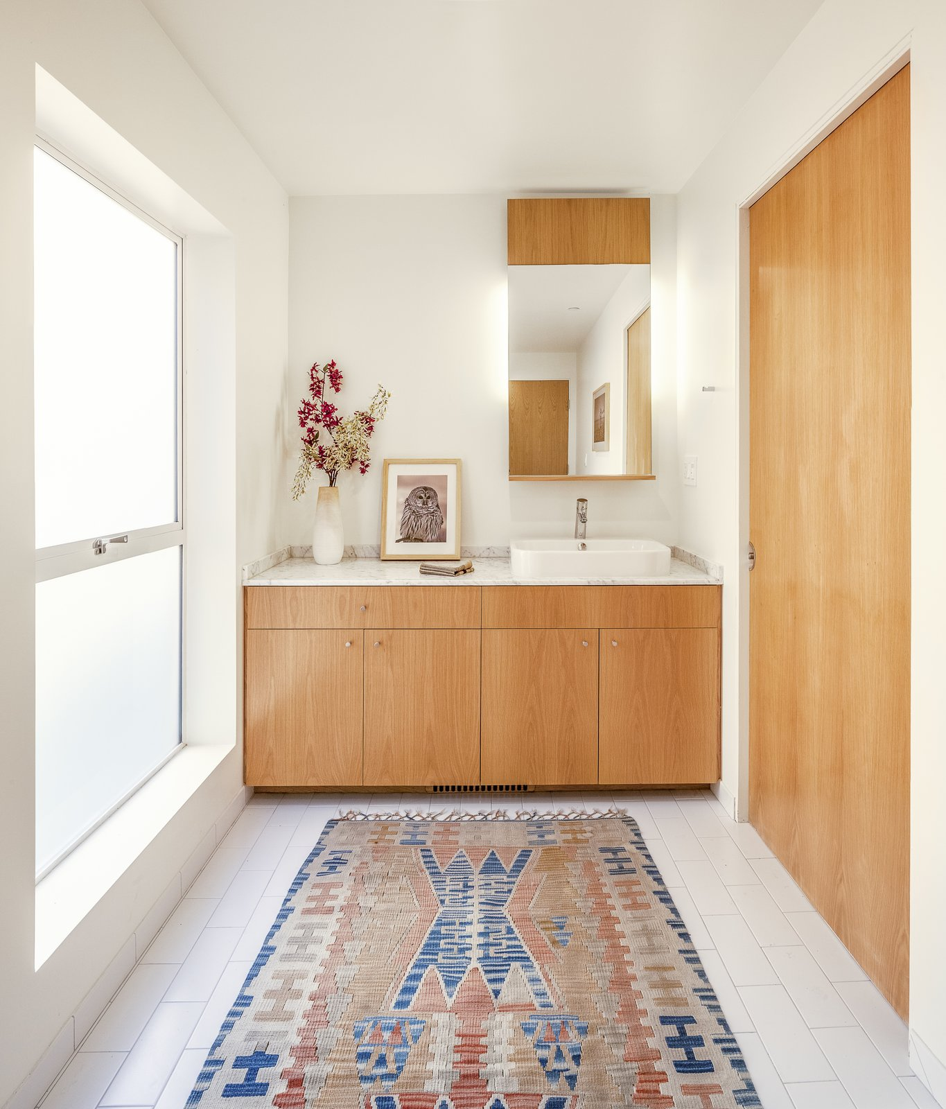 The architect has a track record of stripping away elements of excess to create simple, livable, and well-lit spaces that feel larger than they are. This downstairs bathroom features a simple white ceramic tiles and a sliding white oak door.  Photo 9 of 9 in Twin Houses on Tiny Lots Stretch Outward for Space
