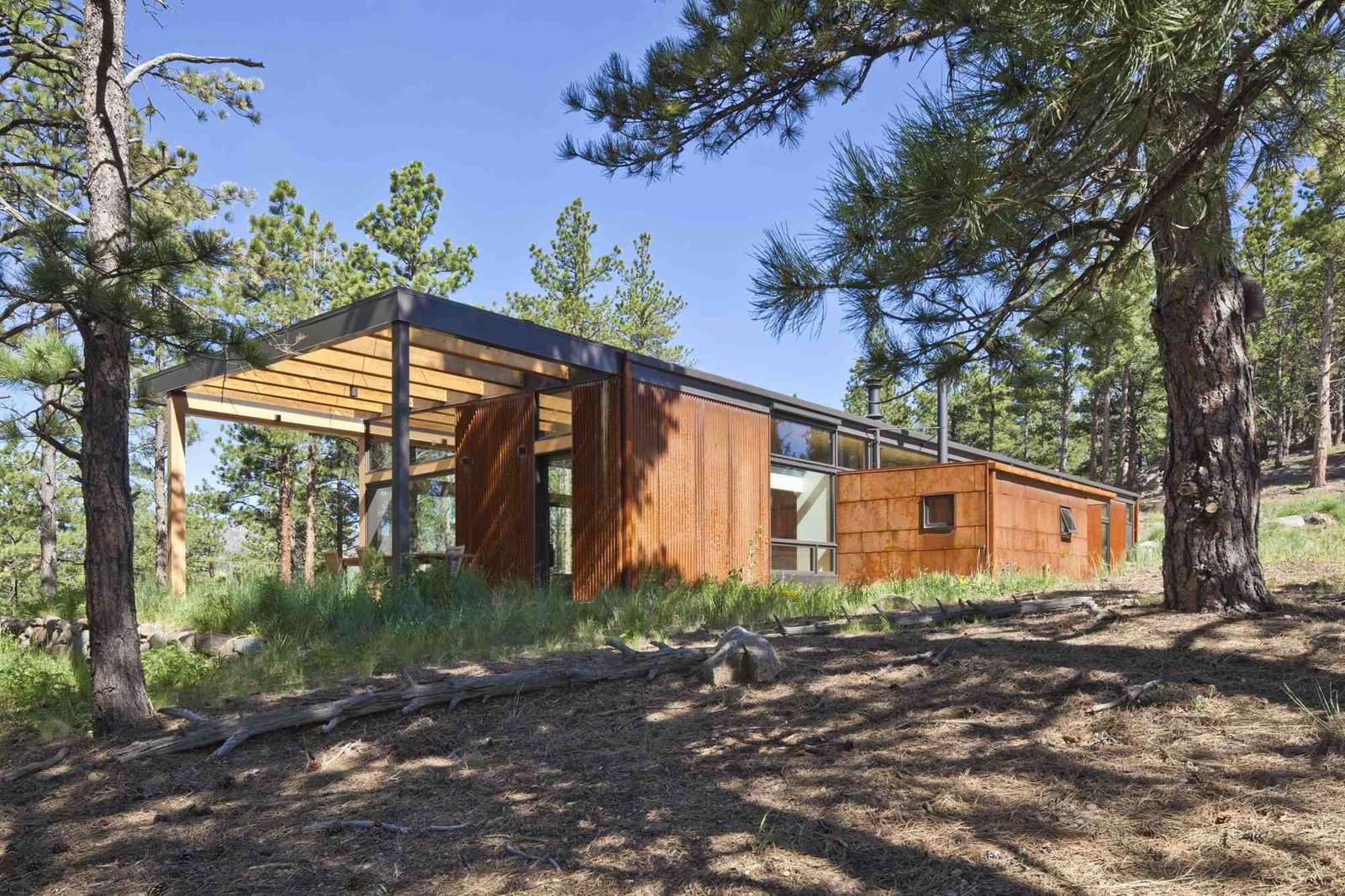 """Exterior, Metal Siding Material, and House Building Type A high band of windows on the east side of the home lets light in, while a simple wood overhang shades an outdoor dining area on the terrace with mountain views. """"On clear days, it feels like you can see across the high plains to Kansas,"""" says Hirsh.   Photo by Ron Johnson.  Cabins & Hideouts from Modern Homes in Colorado"""