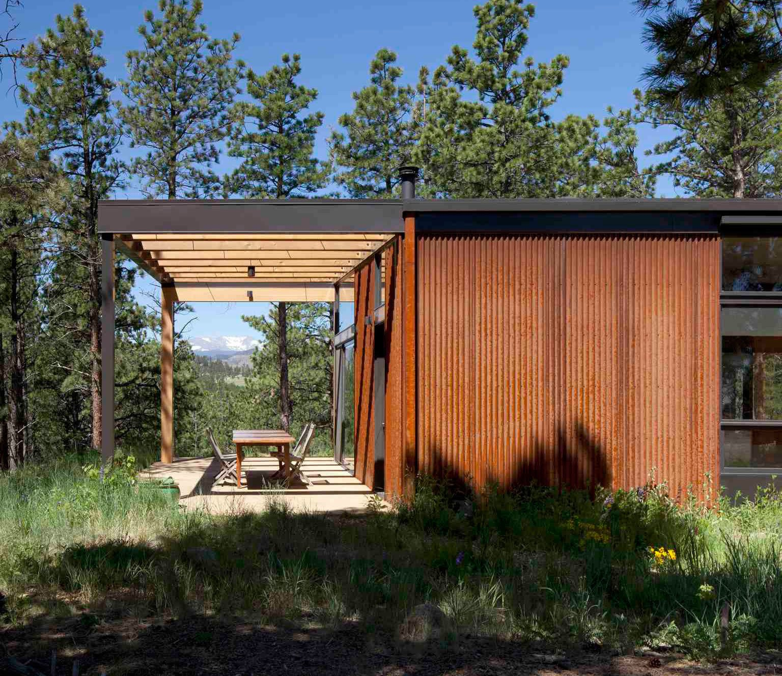 """Exterior, Metal Siding Material, and House Building Type Beyond the terrace, the backs of the Flatiron Peaks reveal themselves. Revegetation of the 35-acre property began immediately following construction of the home—a 2,500-square-foot structure that blends into its woodsy surroundings.   Photo by Ron Johnson.  Search """"terrace"""" from Serene, Sustainable Home in Colorado"""