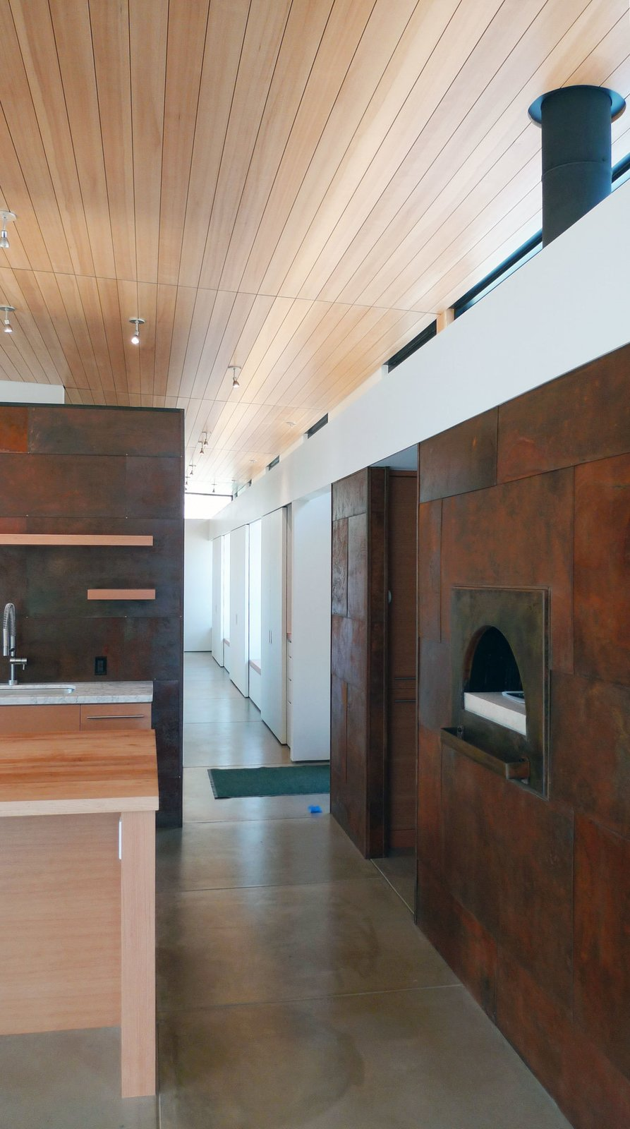 """Kitchen A pizza oven and built-in storage spaces line a hallway, saving space. """"6,000-square-foot houses for single families don't make sense ecologically—or in my opinion, functionally,"""" says Hirsh. """"The house is a nice size for our life—plenty large, but not unwieldy.""""  Photo by Ron Johnson.  Photo 6 of 10 in A Serene, Sustainable Home in Colorado from Serene, Sustainable Home in Colorado"""