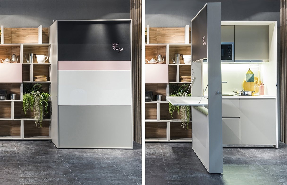 In its closed position, the piece looks like a storage unit. A door on wheels slides open to reveal a kitchen inside.  Shelves from Genius Unfolding Kitchen Tucks Neatly Into Small Spaces
