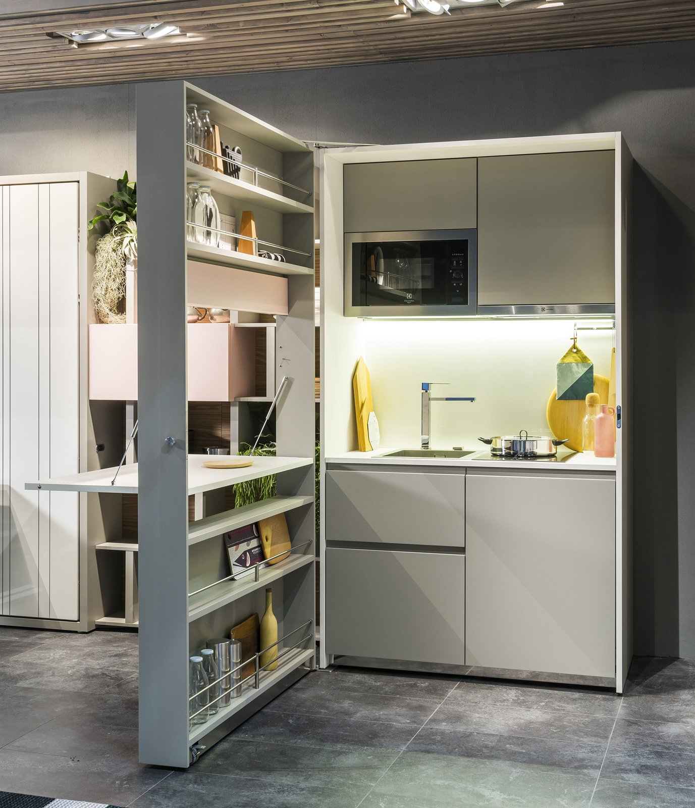 The Box Kitchen contains two burners, a ventilation hood, a sink, a dishwasher, and a microwave. A fold-down laminated countertop creates a prep surface.  Shelves from Genius Unfolding Kitchen Tucks Neatly Into Small Spaces