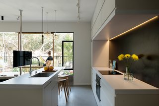 In the kitchen, the custom cabinets contain special compartments that hide appliances from sight. The room draws in natural light from the balcony.