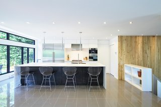 The kitchen features a wide Corian countertop and Bertoia stools. The polished ceramic flooring is from Céramique Décor in Québec.