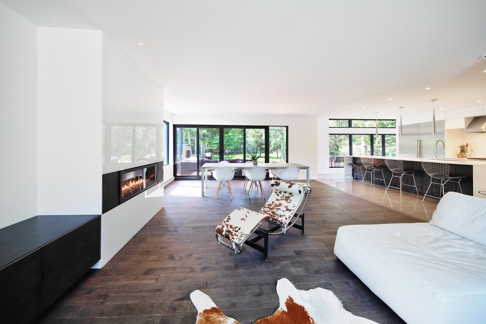 """Living Room and Recliner The dining table in the open-plan space is custom, and the fireplace is from Napoleon.  Search """"outdoorroom-type--living-space"""" from Sleek Renovation on a Tree-Lined Street in Quebec City"""