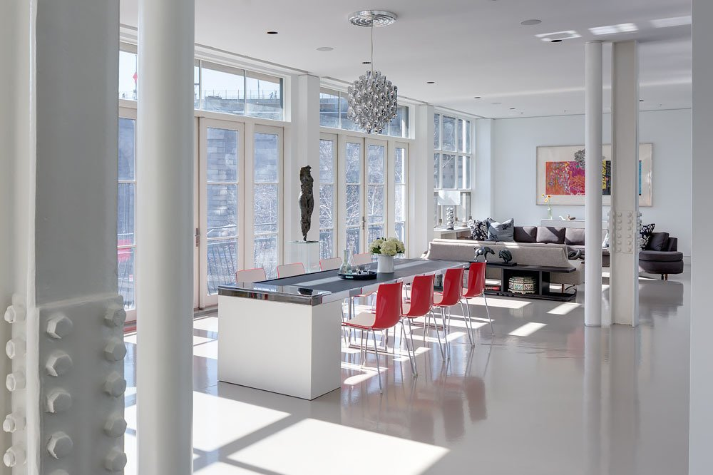 "Light is invited into the home through the 75-foot wall of windows in the main living area. Kopel's favorite part of the home is ""the changing quality of light"" that ""animates the living space"" from day to day and season to season. Lucifer architectural lighting and Polk Audio in-wall speakers add understated function.  A Bright Brooklyn Loft with an Envy-Inducing Walk-In Closet by Sarah Akkoush"