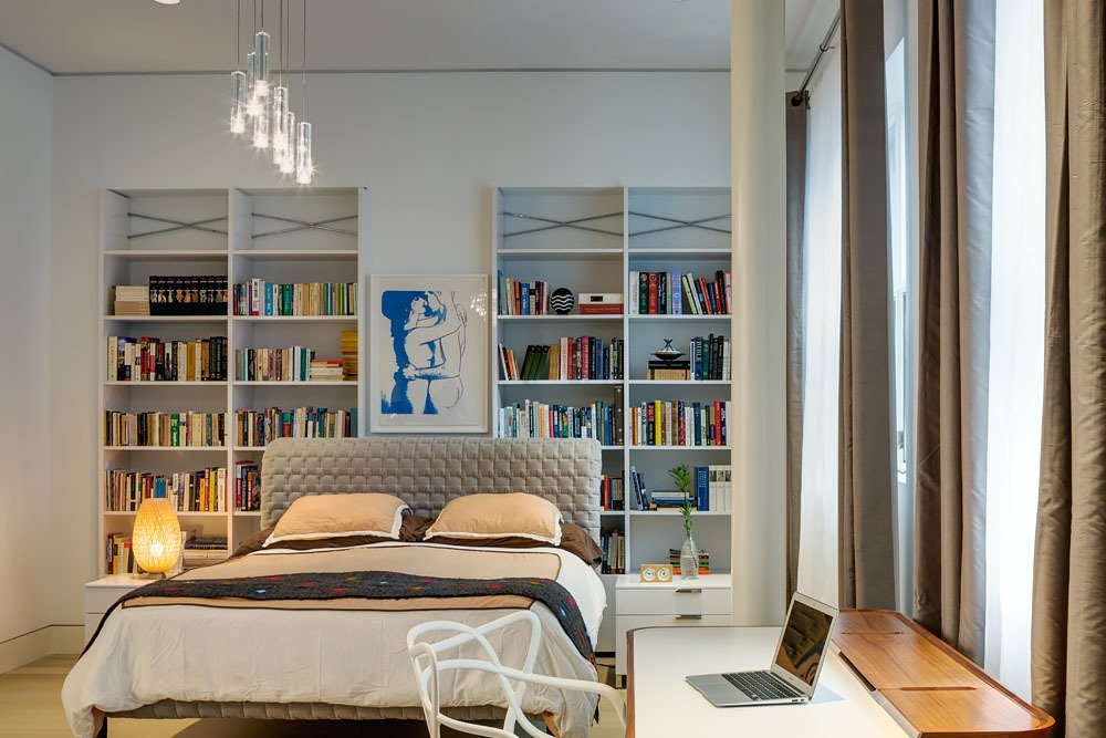 In the master bedroom, a small workstation is accented by a Philippe Stark desk chair, and repurposed white shelving offers generous display space. Ten foot ceilings and expansive windows add to the open and airy feel of the room.  Bedrooms by Dwell