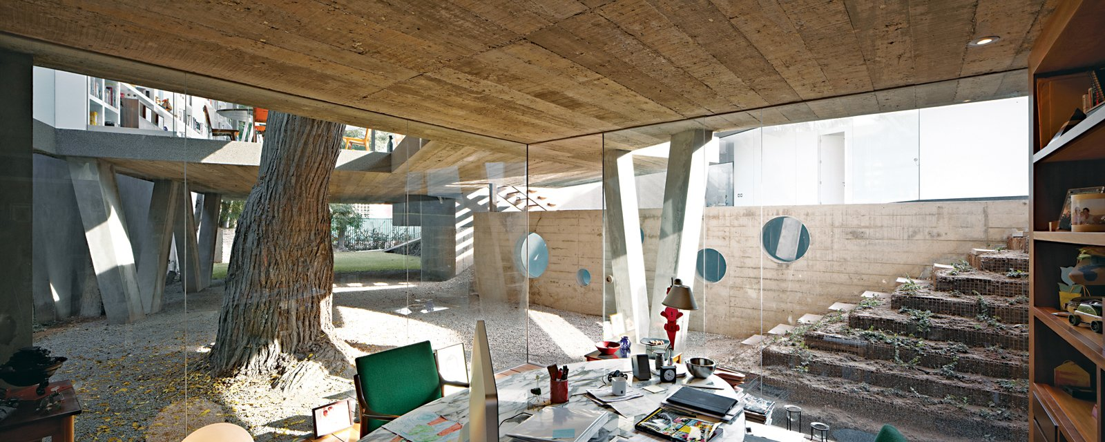Office, Chair, Desk, and Bookcase For a family in Lima, a team from local firm 51-1 Arquitectos built Casa Serpiente, which meanders around 25 existing trees. Husband Irzio's study is among the few ground-level rooms in the 4,300-square-foot house.  Best Photos from A Modern Concrete Home in Peru
