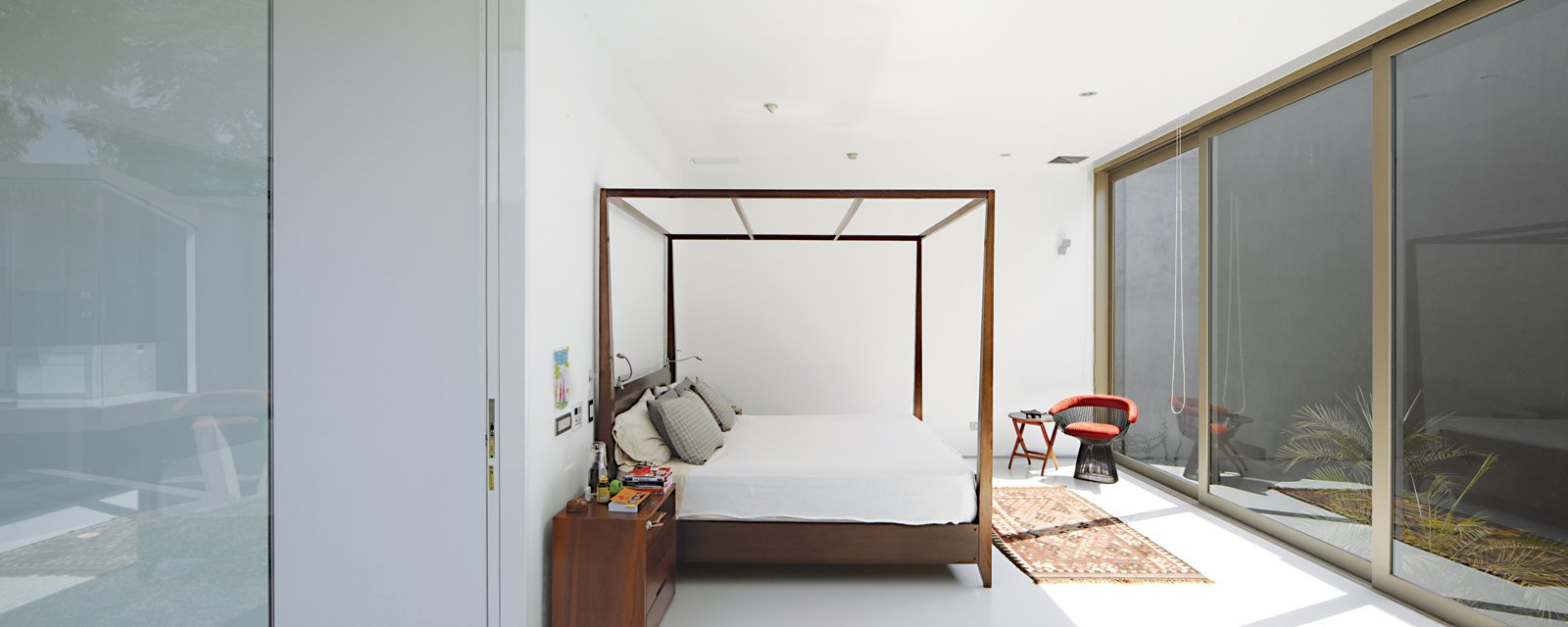 Bedroom, Bed, Dresser, and Chair In the master bedroom is a four-poster bed by Javier Rubio and a vintage Warren Platner chair.  Photos from A Modern Concrete Home in Peru