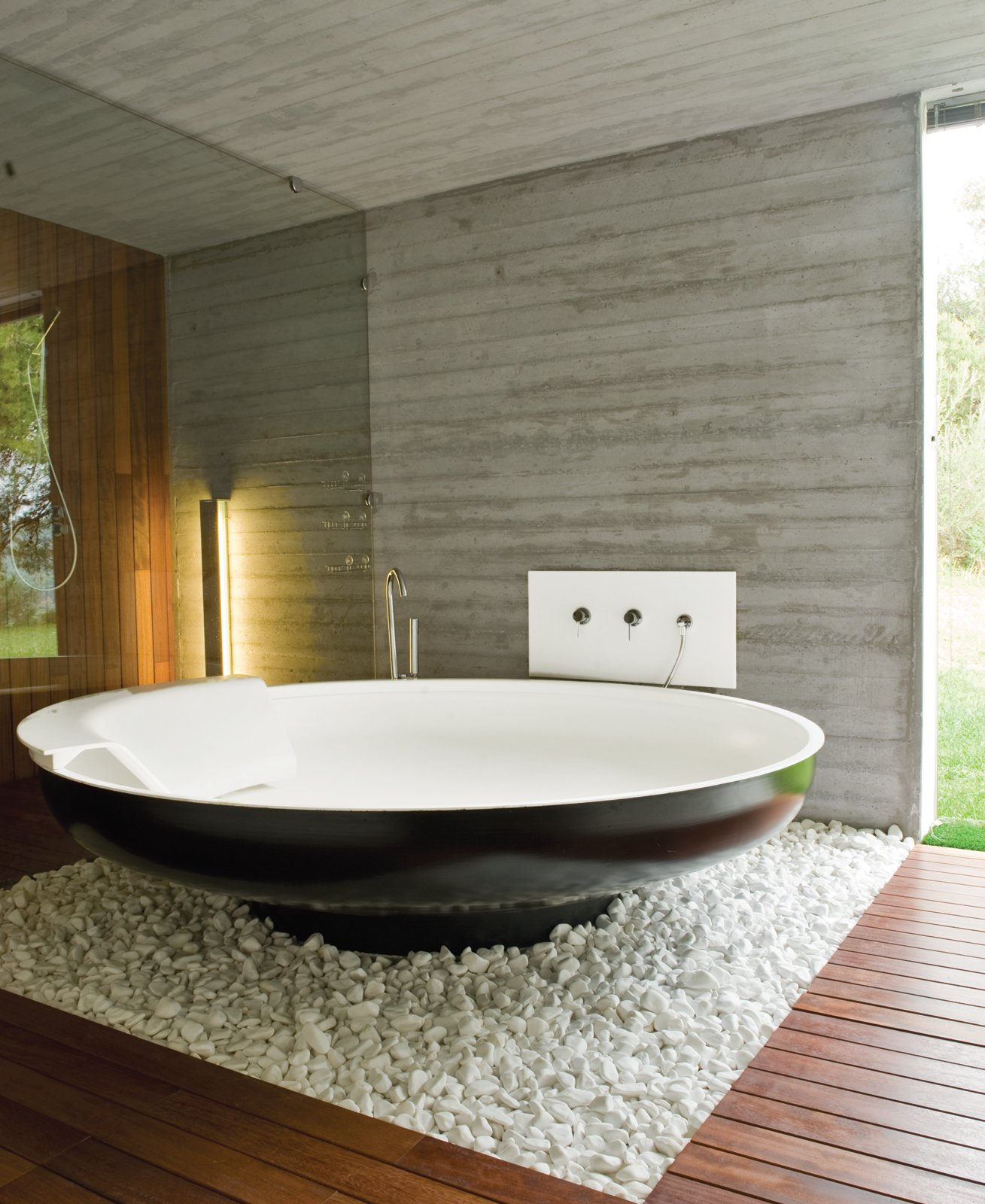 Bath Room, Concrete Wall, and Freestanding Tub A UFO bathtub by Benedini Associati for Agape lends an alien touch to one of the master bathrooms.  Photo 5 of 11 in 10 Ideas For Designing With a Modern Bathtub from An Idyllic Vacation Home in Greece