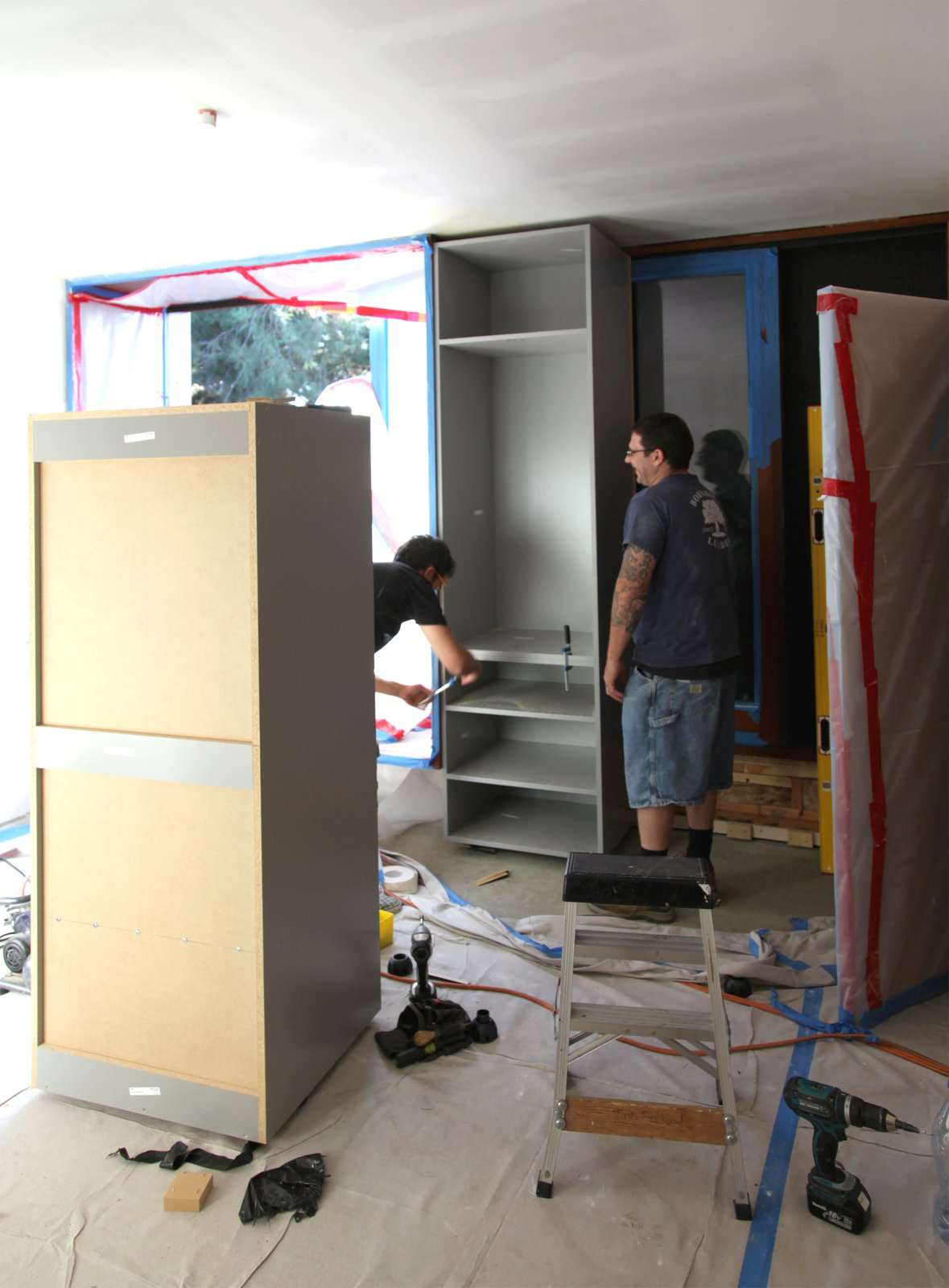 The Semihandmade team installs wardrobe cabinets in an upstairs guest bedroom.  Photo 9 of 17 in Dwell Home Venice: Part 18