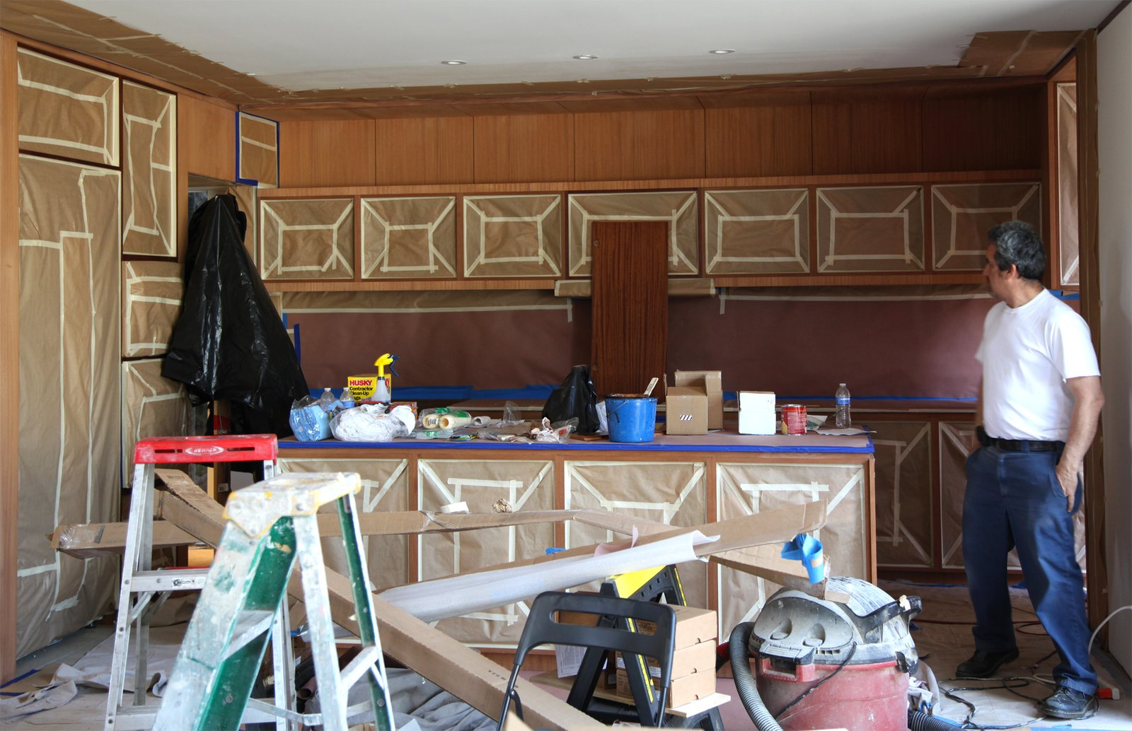 Preparing to stain the kitchen cabinets. The ceiling drywall and all cabinet openings are papered and taped to keep the stain contained..  Photo 13 of 17 in Dwell Home Venice: Part 18