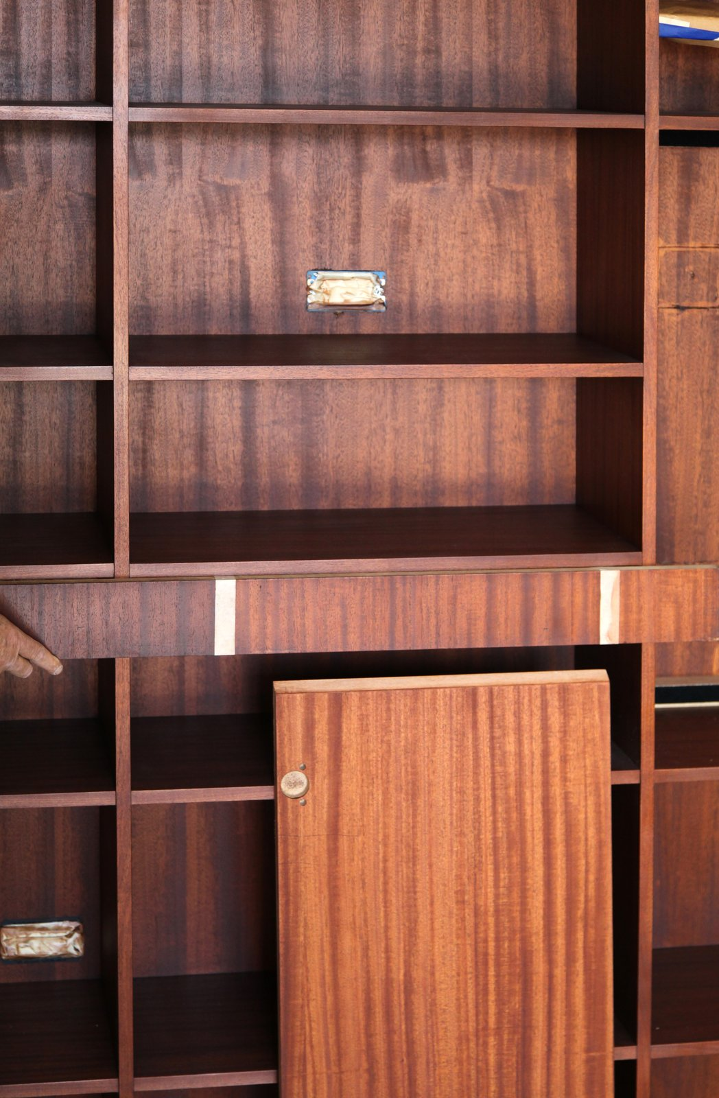 Comparing the first coat of stain on the living room bookshelf against sample stains. The final sealer coat will bring out the warmth of the mahogany color, amplifying any amber tones.  Photo 14 of 17 in Dwell Home Venice: Part 18