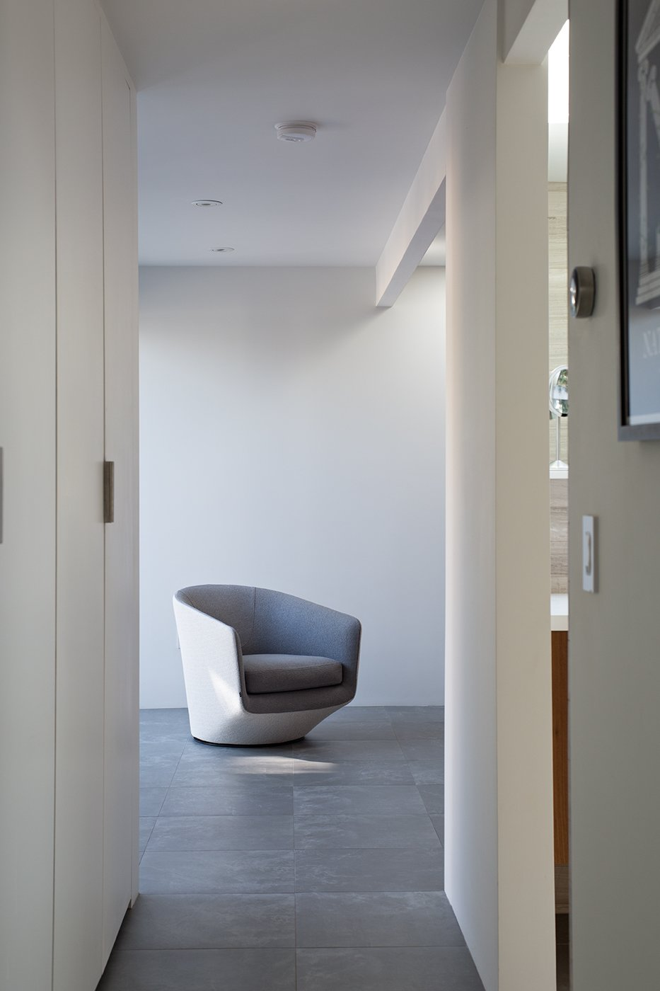 Hallway and Porcelain Tile Floor The floors are covered in two-foot square Nextra Piombo tiles by Monocibec. A U-Turn chair designed by Niels Bendtsen echoes the crisp, sculptural qualities of the interior spaces.  Photo 5 of 8 in Indoor-Outdoor Home by a Midcentury Master Gets a Faithful Update