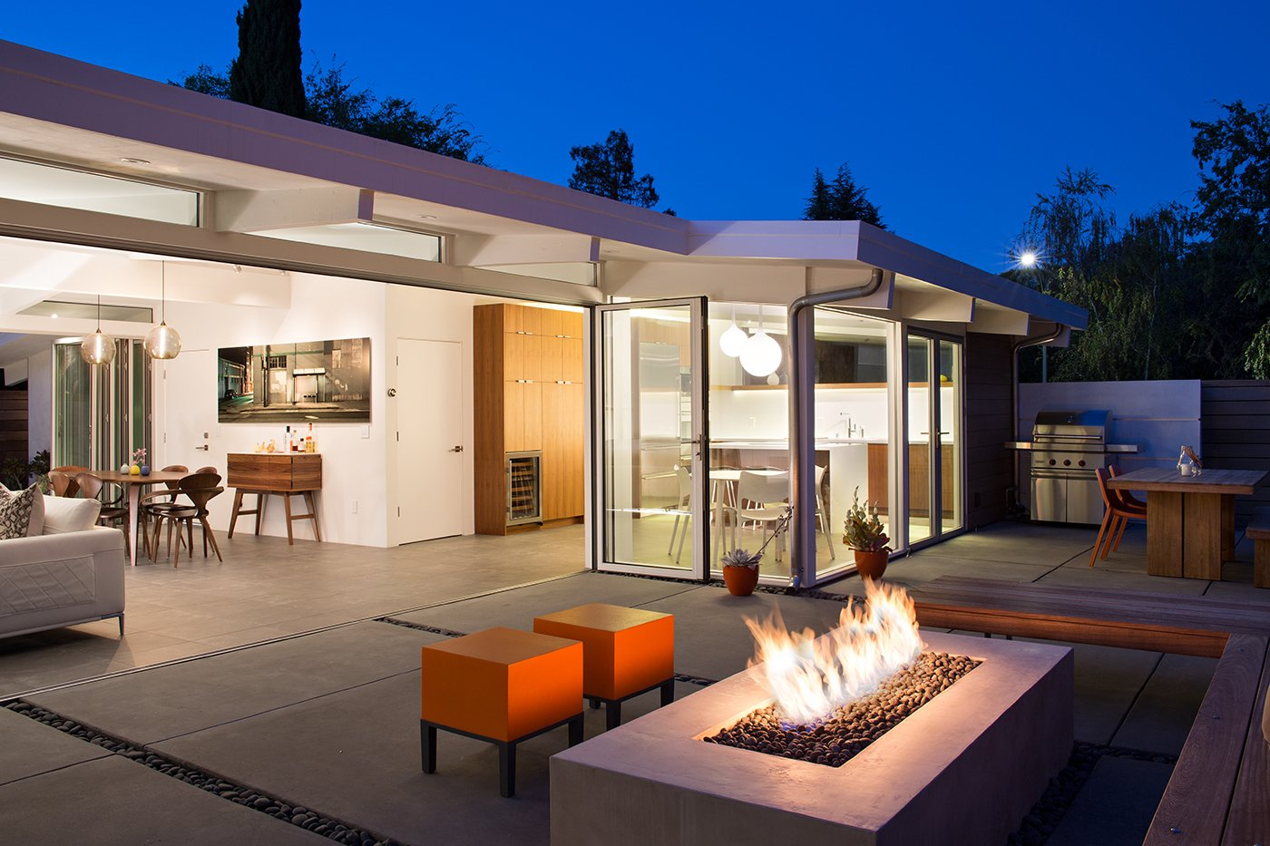 Exterior, Mid-Century Building Type, and House Building Type In the outdoor living area, orange Primary Pouf stools by Quinze & Milan and an ipe bench surround the central fire pit. An outdoor kitchen neighbors its interior counterpart. In addition to a grill, it accommodates a table and bench by Kayu.  Modern Eichler Renovations by Allie Weiss from Indoor-Outdoor Home by a Midcentury Master Gets a Faithful Update