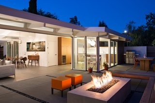 In the outdoor living area, orange Primary Pouf stools by Quinze & Milan and an ipe bench surround the central fire pit. An outdoor kitchen neighbors its interior counterpart. In addition to a grill, it accommodates a table and bench by Kayu.