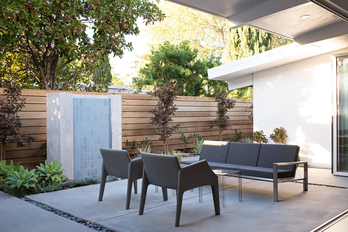 Outside, a contemplative sitting area centers on a fountain clad in tiles by Heath Ceramics. A Case Study Stainless couch by Modernica and Magic Hole armchairs by Kartell are positioned around Jolly side tables by Kartell.  Photo 8 of 8 in Indoor-Outdoor Home by a Midcentury Master Gets a Faithful Update