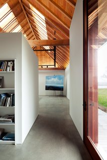 """A glass door on the north side sits opposite a glass window on the south wall that overlooks a birch tree forest. Skylights pull light into the interior. """"Even though the artist paints landscapes, she didn't want to be distracted by the beauty of her surroundings while in the studio, which led to the limited apertures,"""" Peterson says."""