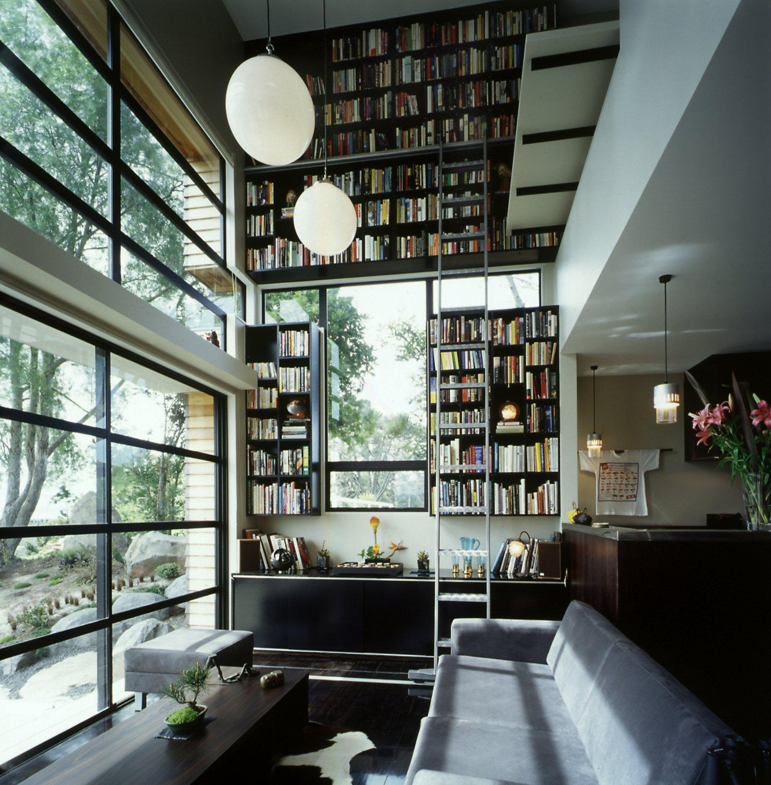Hughes' collection of hundreds of books is stored on a vertiginous two story bookcase, which takes up the whole of the northern wall of the living room. It's an ingenious solution to the small-space dwelling that draws the eye up, adding texture and interest to the room without taking up floor space.  bookcase