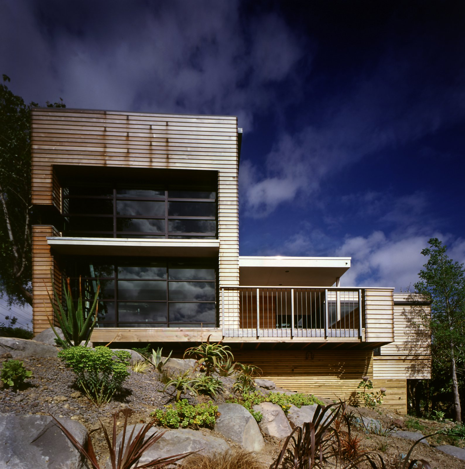 "The home's Canadian cedar cladding and aluminium joinery is low-maintenance, and designed to weather gently over time. The natural finish blends well with the surrounding garden, with its sculptural, desert plants. ""We face south-west, so the weather comes straight at us, and the wind is loaded with salt,"" says Hughes. ""Fortunately, the plants we liked don't give a hoot about the wind.""  Search ""stockholm elevations architectural print"" from This Japanese-Style Box Home Boasts a Two-Story Bookcase"