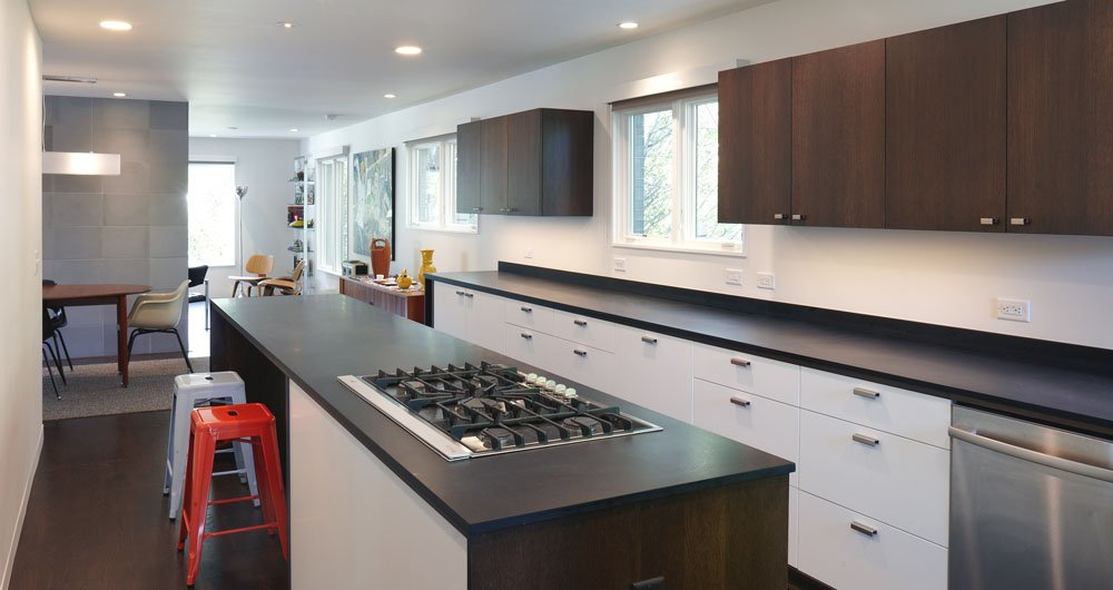 Paperstone countertops and custom cabinets outfit the kitchen. The cooktop is by Whirlpool.  Photo 4 of 6 in Renovating a Modern House in a Historic District