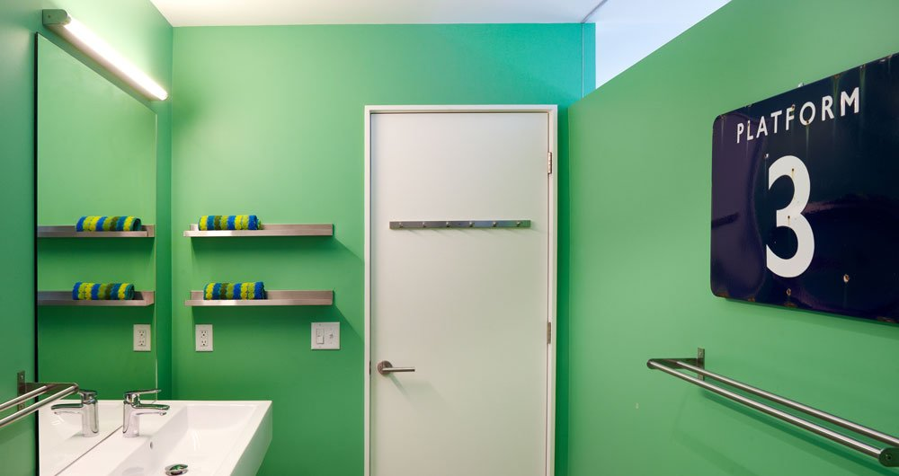 Bright paint in the bathroom offsets the white living room. A transom brings natural light into the space. The faucets are Grohe Europlus.  Photo 5 of 6 in Renovating a Modern House in a Historic District
